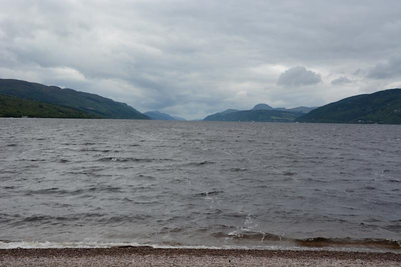 In the foreground is a small strip of pebbles, some of which has been washed by the water lapping over them. Then we have the large expanse of Loch Ness, by volume the largest freshwater loch in Scotland, looking dark and imposing with its very murky water, due to a high peat content. We can see the down the 23 mile length of Loch Ness, which is surrounded by hills and mountains. The loch follows the line of the Great Glen Fault, and is reputed to hold the famous Loch Ness Monster, or Nessie as it is affectionately known. Loch Ness is located just outside Inverness in the Highlands of Scotland