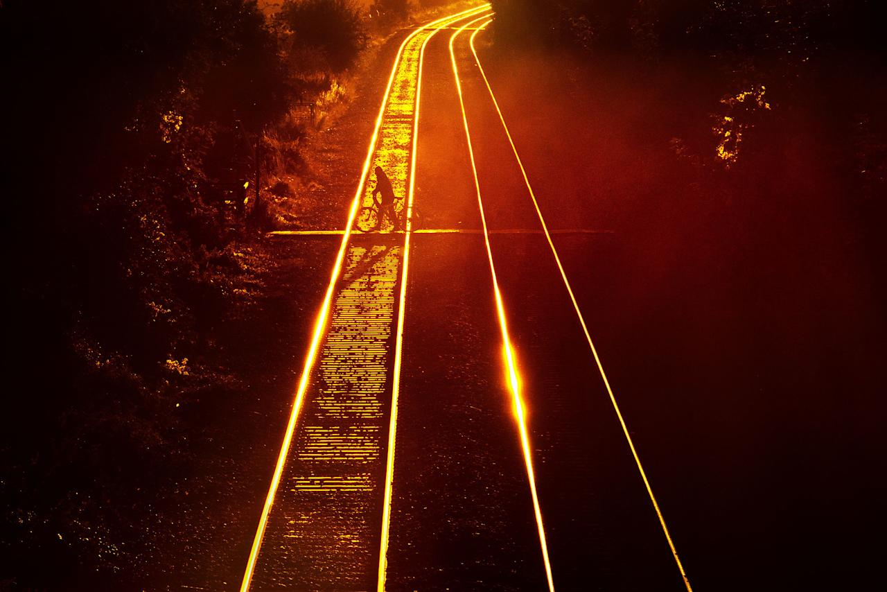 <p>A cyclist is silhouetted as he crosses train tracks at Bingham, Nottinghamshire. [Picture: PA] </p>