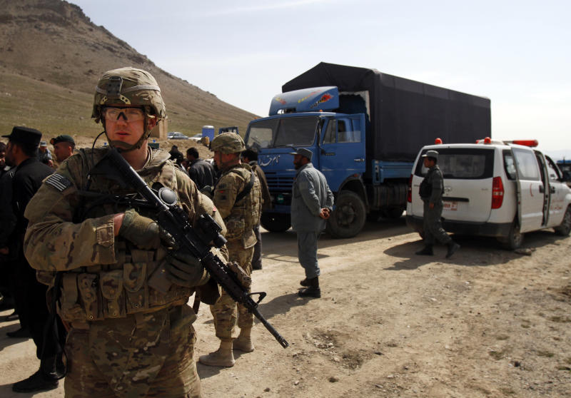 A U.S. soldier secures the scene after U.S. forces shot on an Afghan truck, center, killing two passengers and injuring another on the road between Kabul and Bagram, Afghanistan, Monday, March 11, 2013. (AP Photo/Ahmad Jamshid)