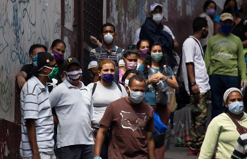 People line up to buy food and disinfectant, some wearing face masks as a preventive measure against the spread of the new coronavirus in Caracas, Venezuela, on March 26, 2020. (Photo: AP Photo/Ariana Cubillos)