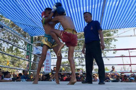 Nanthawat Pomsod (C), 11, who is a child boxer, fights Kritthonglek Sitkritthongkam (L) during a boxing match at a temple in Buriram province, Thailand, February 2, 2018. REUTERS/Prapan Chankeaw