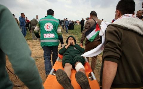 A Palestinian youth being carried on a stretcher after being injured during demonstrations on Friday - Credit: MOHAMMED ABED/AFP