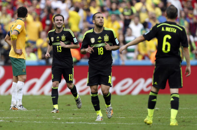 Spain's Juan Mata, second left, smiles after scoring his side's third goal during the group B World Cup soccer match between Australia and Spain at the Arena da Baixada in Curitiba, Brazil, Monday, June 23, 2014. (AP Photo/Jon Super)