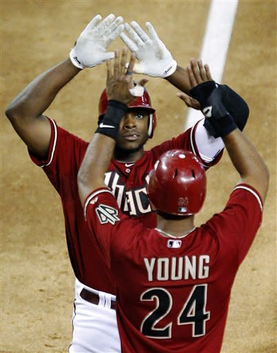 Arizona Diamondbacks' Justin Upton greets Chris Young (24) at home plate after Upton hit a three-run home run against the Seattle Mariners during the fifth inning of an interleague baseball game, Wednesday, June 20, 2012, in Phoenix. (AP Photo/Matt York)