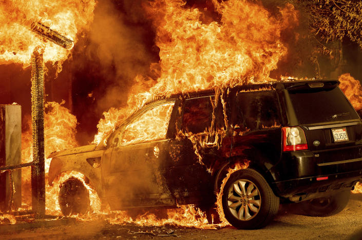 Flames consume a vehicle as the Sugar Fire, part of the Beckwourth Complex Fire, tears through Doyle, Calif., Saturday, July 10, 2021. Pushed by heavy winds amid a heat wave, the fire came out of the hills and destroyed multiple residences in central Doyle. (AP Photo/Noah Berger)