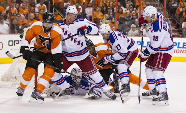 New York Rangers' Henrik Lundqvist, bottom center, of Sweden, covers up the puck as Anton Stralman, center left, of Sweden, deals with Philadelphia Flyers' Scott Hartnell, left, and Rangers' Ryan McDonagh, right center, defends Flyers' Wayne Simmonds center, while Rangers' Brad Richards, right, looks for the puck during the second period in Game 3 of an NHL hockey first-round playoff series, Tuesday, April 22, 2014, in Philadelphia. (AP Photo/Chris Szagola)
