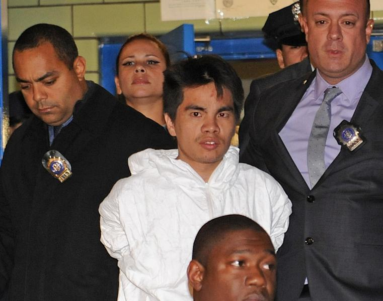 Mingdong Chen, a suspect in the murder of a five people in Brooklyn's Sunset Park neighborhood, is walked by police from the 66th precinct, Sunday, Oct. 27, 2013 in New York. The Chinese immigrant, who neighbors said struggled to survive in America, was arrested in the stabbing death Saturday night of his cousin's wife and her four children. (AP Photo/ Louis Lanzano)
