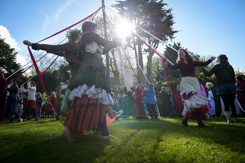 People take part in the traditional maypole dance at the Chalice Well, Glastonbury, where Beltane festivities are taking place on May Day.