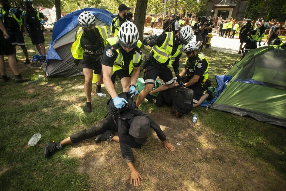 A police officer kneels on the back of a protester in a homeless encampment