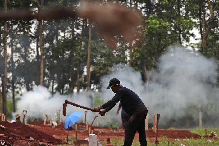 A gravedigger prepares a grave for a COVID-19 victim at Cipenjo cemetery in Bogor, West Java, Indonesia, Wednesday, July 14, 2021. The world's fourth most populous country has been hit hard by an explosion of COVID-19 cases that have strained hospitals on the main island of Java.(AP Photo/Achmad Ibrahim)