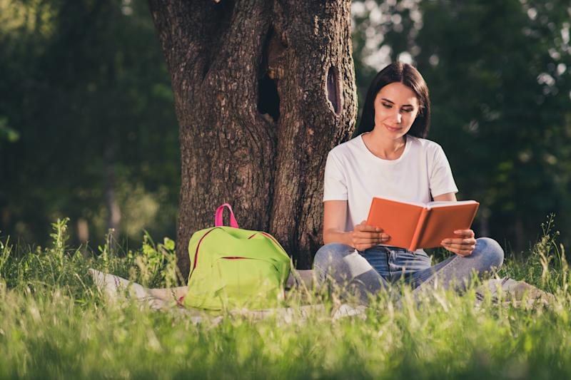 Portrait of her she nice attractive pretty focused girl reading novel interesting, academic book sitting on lawn green color grass veil duvet spending sunny day weekend