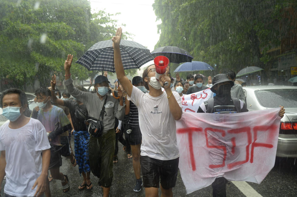 Anti-coup protesters flash the three-finger salute and chant slogans during a demonstration against the military coup in the rain at Pabedan township in Yangon, Myanmar, Friday, April 30, 2021. (AP Photo/Vincent Thian)