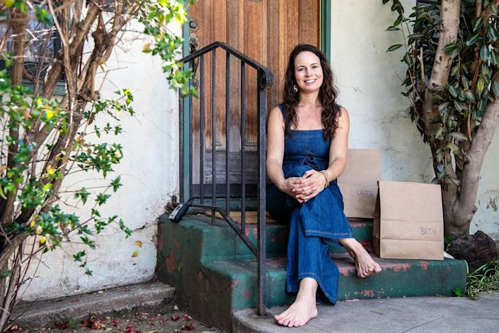 Meredith Klein sits on steps with brown paper grocery bags