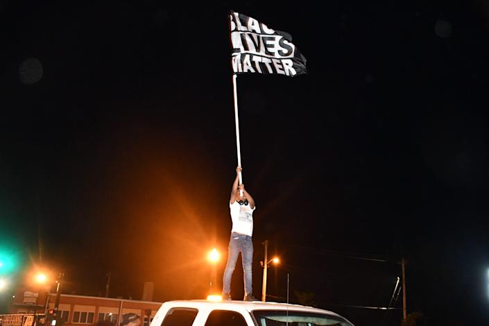 A child holds a Black Lives Matter flag during an eighth night of protest in Elizabeth City, N.C., after a judge ruled Wednesday not to release bodycam footage of sheriff's deputies fatally shooting Andrew Brown Jr.