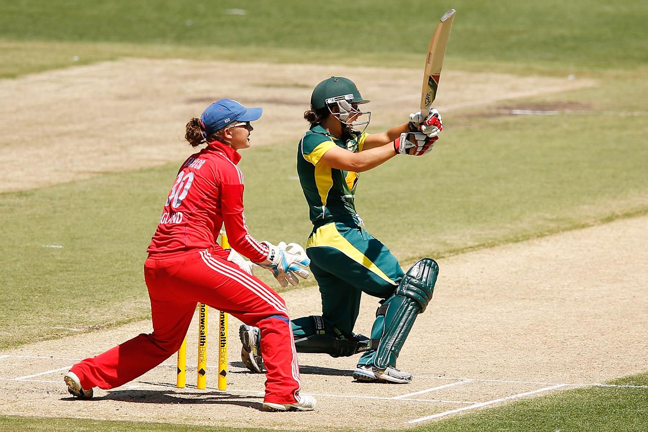 MELBOURNE, AUSTRALIA - JANUARY 23:   Nicole Bolton of Australia plays a shot as Sarah Taylor of England looks on during game 2 of the Australia v England Women's one day international series, January 23, 2014 in Melbourne, Australia.  (Photo by Darrian Traynor/Getty Images)