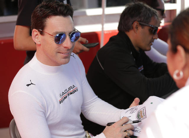 Acura Team Penske driver Simon Pagenaud signs autographs before the Rolex 24 hour auto race at Daytona International Speedway, Saturday, Jan. 25, 2020, in Daytona Beach, Fla. (AP Photo/Terry Renna)