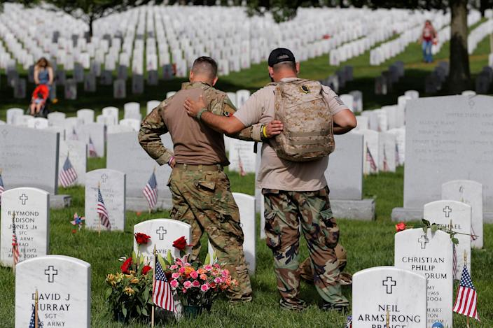 <p>MAY 30, 2016 — U.S. Army soldiers Rick Kolberg (L) and Jesus Gallegos embrace as they visit the graves of Raymond Jones and Peter Enos on Memorial Day at Arlington National Cemetery in Washington. (Lucas Jackson/Reuters) </p>