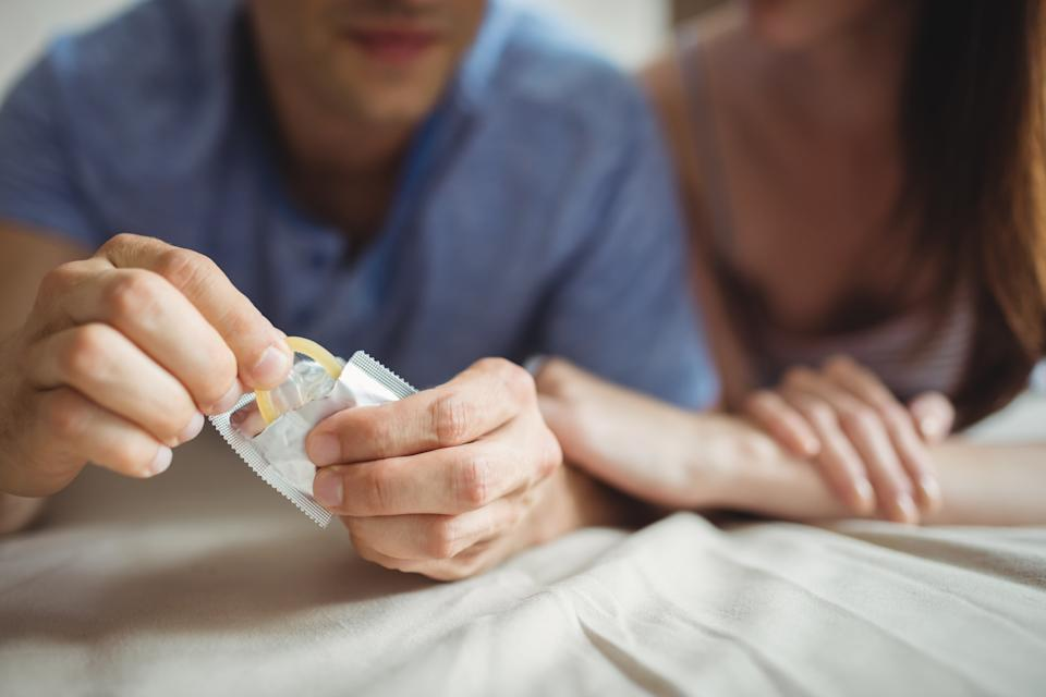 Close-up of couple with a condom on bed in the bedroom