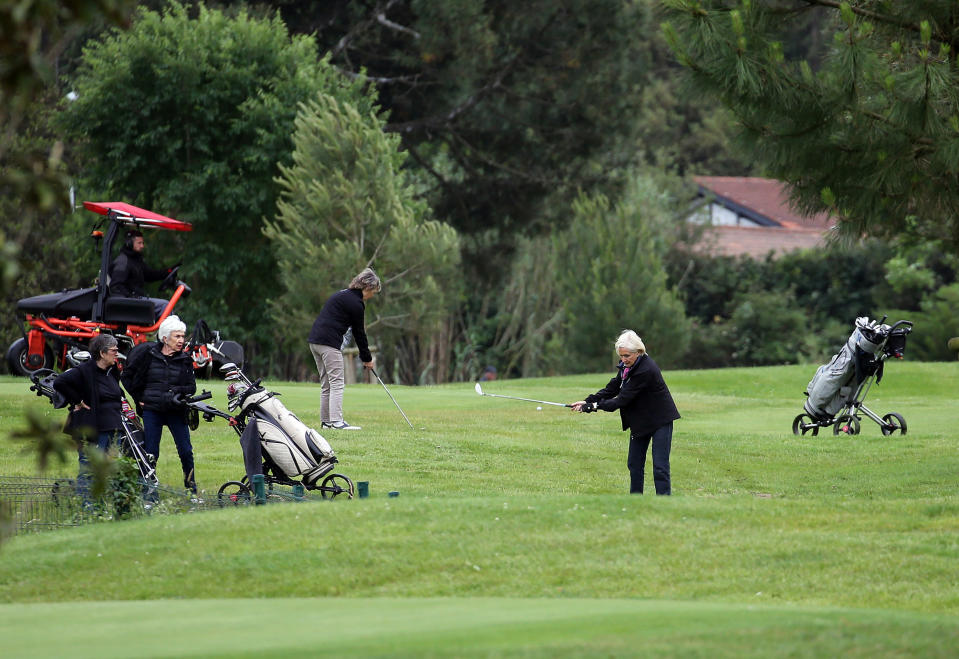 People play golf at the Imperatrice golf course in Biarritz, southwestern France, Tuesday, May 12, 2020. As part of France's gradual re-opening process, the government is allowing the resumption this week of a few select sports that don't involve close physical contact, including golf, tennis and horse racing. Up until this week only individual sports such as jogging were allowed, and indoor sports facilities remain closed to prevent spread of the virus. (AP Photo/Bob Edme)