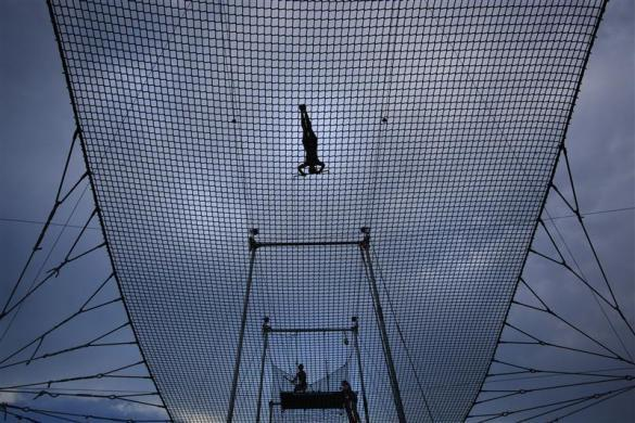 A trapezist swings above the net at Trapeze School New York July 1, 2012.