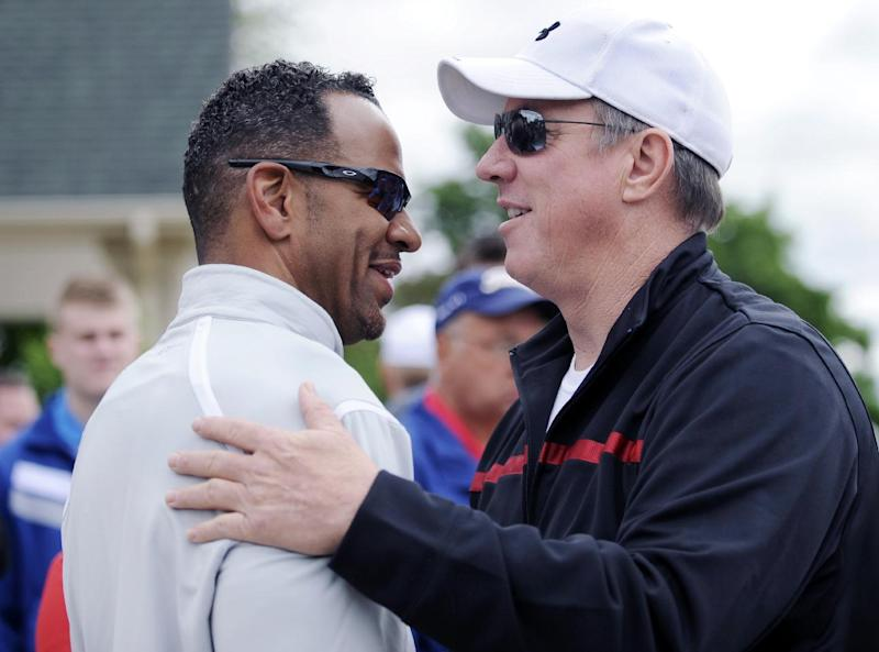 Andre Reed and Jim Kelly greet one another before a press conference in Batavia, N.Y. , Monday June 3, 2013. Kelly says he has been diagnosed with cancer in his upper jaw bone and will have surgery on June 7. (AP Photo/Gary Wiepert)