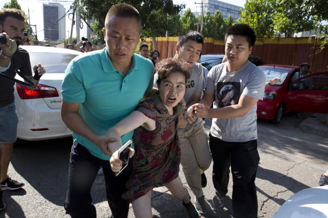 <p>A woman is dragged away by Chinese men moments after she was seen talking to journalists near the site of a reported explosion outside the U.S. Embassy in Beijing, Thursday, July 26, 2018. (Photo: Ng Han Guan/AP) </p>