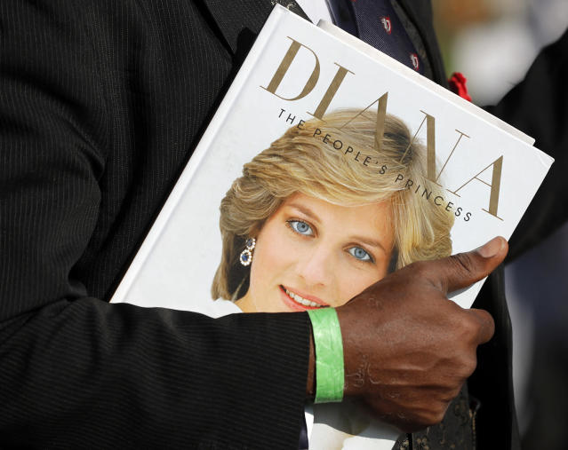 <p>A royal fan holds a book to remember the late Diana, Princess of Wales, outside Kensington Palace in London, Aug. 31, 2017. (Photo: Frank Augstein/AP) </p>