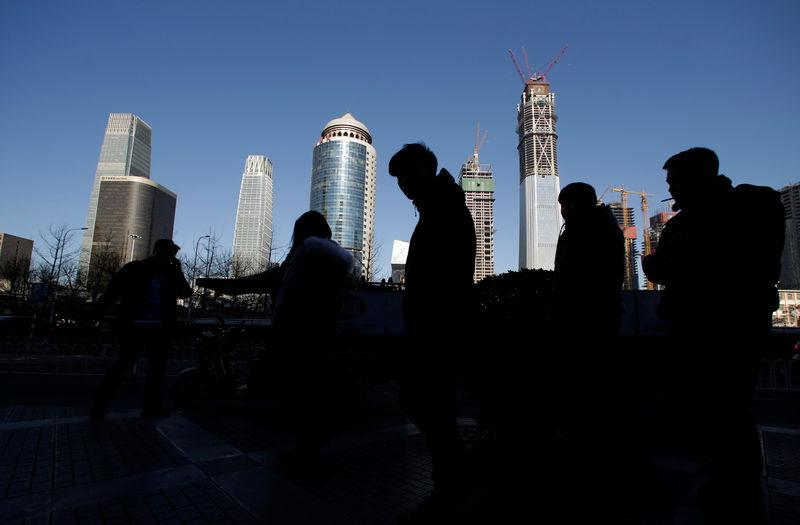 Pedestrians walk outside an office building in Beijing's central business area