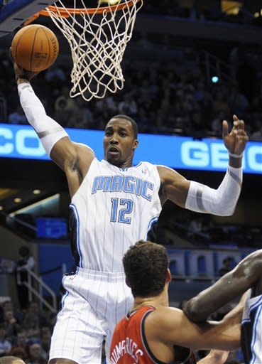 Orlando Magic center Dwight Howard (12) grabs a rebound in front of New Jersey Nets forward Kris Humphries during the first half of an NBA basketball game in Orlando, Fla., Thursday, Dec. 29, 2011. (AP Photo/Phelan M. Ebenhack)