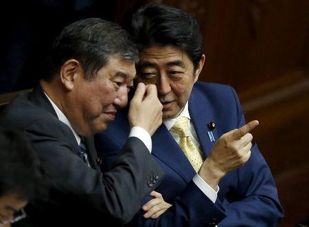 FILE PHOTO : Japan's Prime Minister Shinzo Abe (R) talks with minister in charge of reviving local economies Shigeru Ishiba during the plenary session of the parliament in Tokyo July 16, 2015. REUTERS/Toru Hanai/File Photo