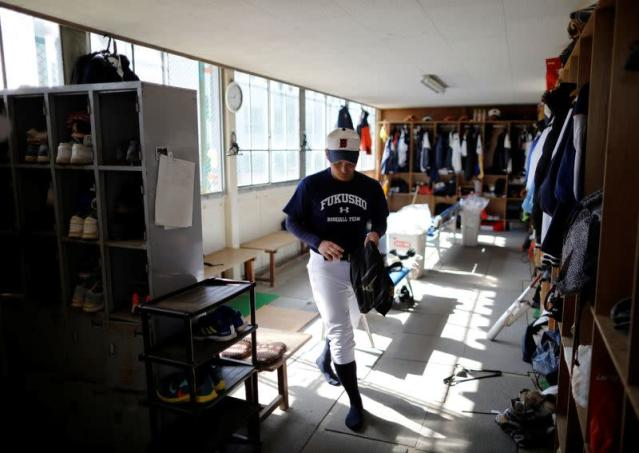 Ryoma Ouchi, an ace pitcher at Fukushima Commercial High School baseball team from Iitate, prepares for a workout at the clubhouse of the team in Fukushima, Japan