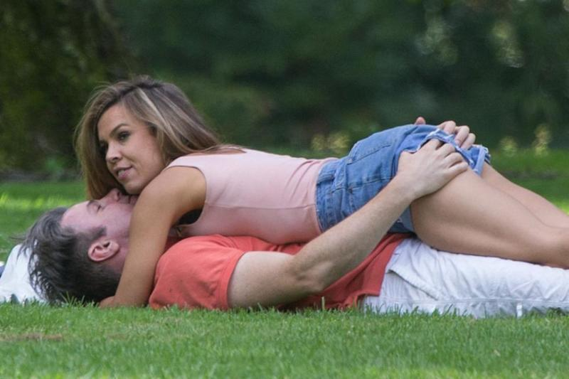 The pair are all smiles as they kiss and cuddle on the grass. Source: Splash