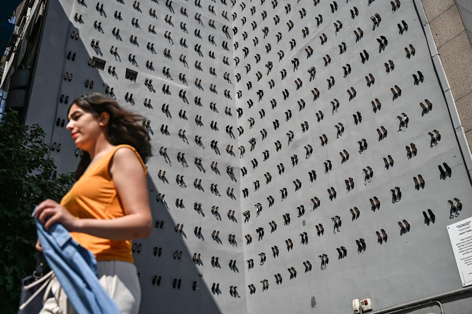 A woman passes in front of a contemporary art installation by Turkish artist Vahit Tuna in an attempt to raise awareness on women killed by domestic violence by their partners and husbands, on September 17, 2019 in Istanbul. - Turkish artist Vahiot Tuna placed 440 pair of female shoes on the walls of a building to symbolize women killed by their partners and husbands in 2018 in Turkey. (Photo by Ozan KOSE / AFP) / RESTRICTED TO EDITORIAL USE - MANDATORY MENTION OF THE ARTIST UPON PUBLICATION - TO ILLUSTRATE THE EVENT AS SPECIFIED IN THE CAPTION        (Photo credit should read OZAN KOSE/AFP/Getty Images)