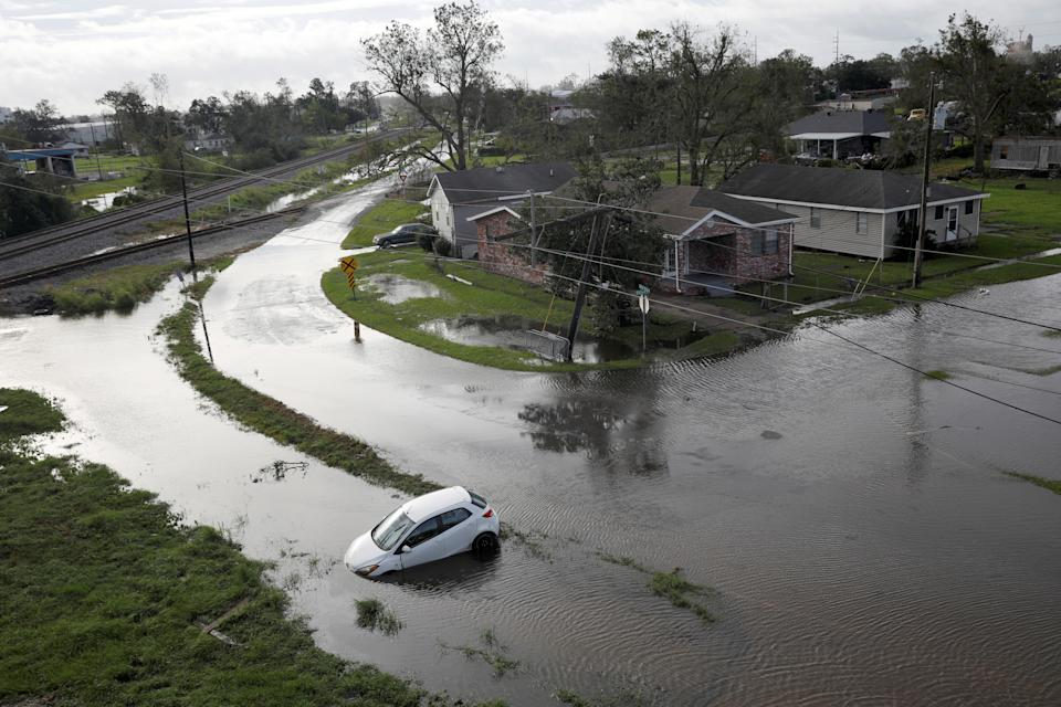 Flooded streets are seen from above with car partially submerged, nose down.