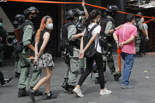 Police detain protesters after a protest in Causeway Bay before the annual handover march in Hong Kong. (AP)