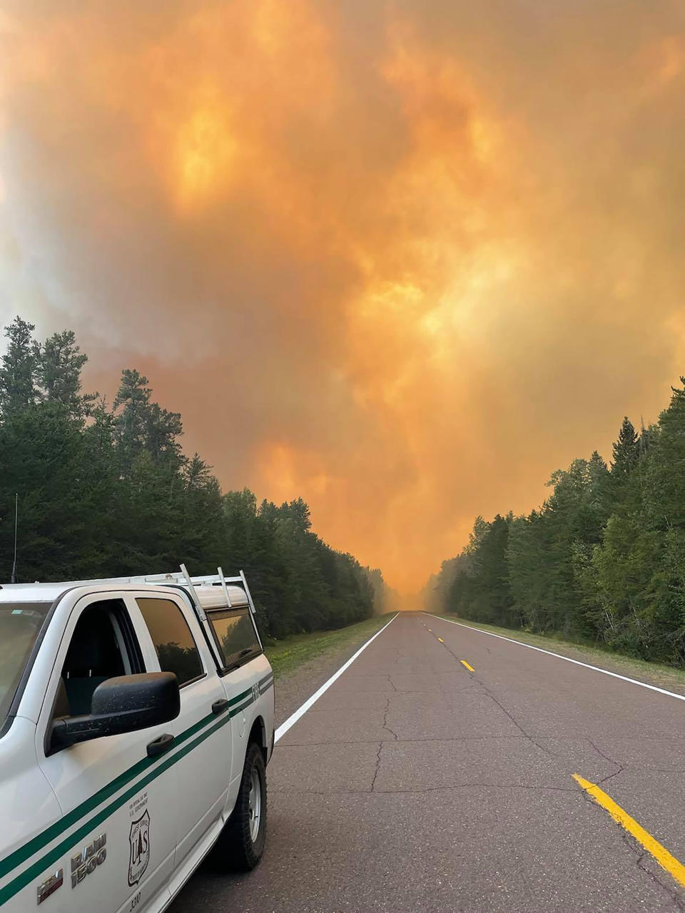This Thursday, Aug. 19, 2021, photo provided by the U.S. Forest Service, a rapidly growing wildfire rises in the background in northeastern Minnesota. U.S. Forest Service officials have warned home and cabin owners who fled a wildfire in northeastern Minnesota that the winds could shift this weekend, putting their properties in danger. Dozens of people got the warning at a public meeting Thursday, Aug. 19, 2021, evening in the small town of Finland, where officials gave them the latest about the Greenwood Lake fire and their strategy for trying to stop it. (Nick Petrack/U.S. Forest Service via AP)