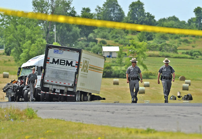 New York State Troopers investigate the scene of a fiery chain-reaction crash in a roadwork zone on Route 11 Thursday, July 19, 2012 in Antwerp, N.Y. Police say a tractor-trailer driven by James A. Mills Jr. of Myerstown, Pa., struck several vehicles that had slowed or stopped on the road. Five died in one SUV. They're identified as 42-year-old Laurie Dana of Lawrence; her daughters, 14-year-old Catelyn and 11-year-old Lauren; 69-year-old Janet Dana; and 14-year-old Shannon Planty. Police say another driver, 59-year-old Maryann Gregory of Dickinson Center, died at a hospital. (AP Photo/The Watertown Daily Times, Amanda Morrison) SYRACUSE OUT