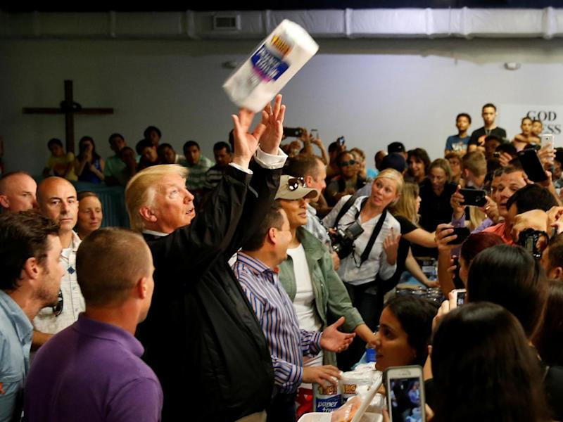 Trump tosses rolls of paper towels to people at a hurricane relief distribution centre at Calvary Chapel in San Juan (Reuters)