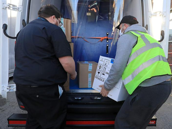 A pharmacy technician from Croydon Health Services takes delivery at Croydon University Hospital in Croydon of the first batch of Covid-19 vaccinations to be delivered to the area (PA)