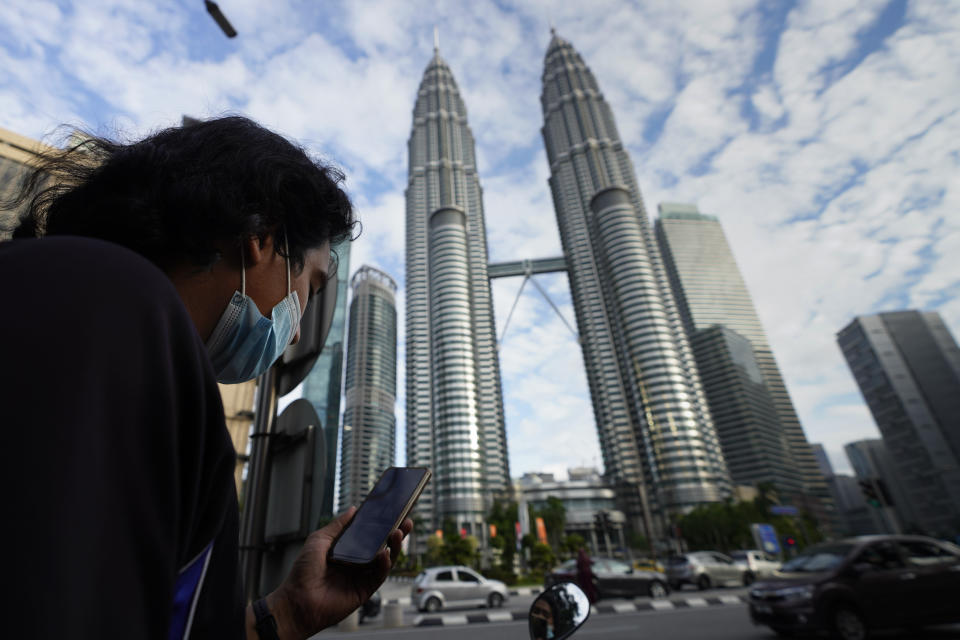 A man wearing a face mask listens to live broadcast in front of Twin Towers in downtown Kuala Lumpur, Malaysia, Monday, Jan. 11, 2021. Prime Minister Muhyiddin Yassin says Malaysia's health care system is at a breaking point as he announced new movement curbs, including near-lockdown in Kuala Lumpur and several high-risk states to rein in a spike in coronavirus cases. (AP Photo/Vincent Thian)