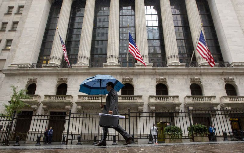 Man carries an umbrella in the rain as he passes the New York Stock Exchange
