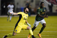 Vancouver Whitecaps FC goalkeeper Maxime Crepeau (16) throws the ball in play against Portland Timbers forward Dairon Asprilla, right, in the first half during an MLS soccer game Sunday, April 18, 2021, in Sandy, Utah. (AP Photo/Rick Bowmer)