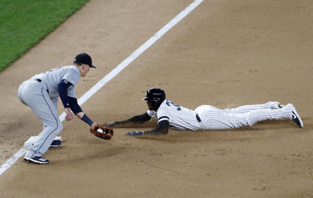 Seattle Mariners third baseman Ryon Healy, left, tags out New York Yankees' Cameron Maybin, who was trying to take two bases on a throwing error at first on a pickoff attempt by Mariners starting pitcher Marco Gonzales during the fifth inning of a baseball game Tuesday, May 7, 2019, in New York. (AP Photo/Kathy Willens)