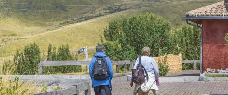 QUITO, ECUADOR, OCTOBER - 2015 - Back view of two elderly women walking on nature in a tour in the highs of Quito, Ecuador