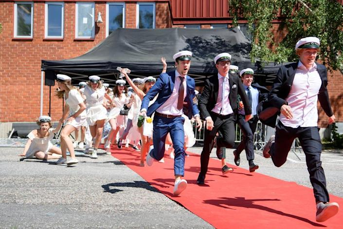 "<div class=""inline-image__caption""> <p>Students run out of their school celebrating their high school graduation at Nacka Gymnasium in Stockholm, Sweden.</p> </div> <div class=""inline-image__credit""> Jessica Gow via Reuters </div>"