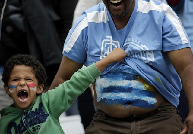 A young boy shows off Uruguay's flag on a man's stomach before the group D World Cup soccer match between Uruguay and England at the Itaquerao Stadium in Sao Paulo, Brazil, Thursday, June 19, 2014. (AP Photo/Felipe Dana)