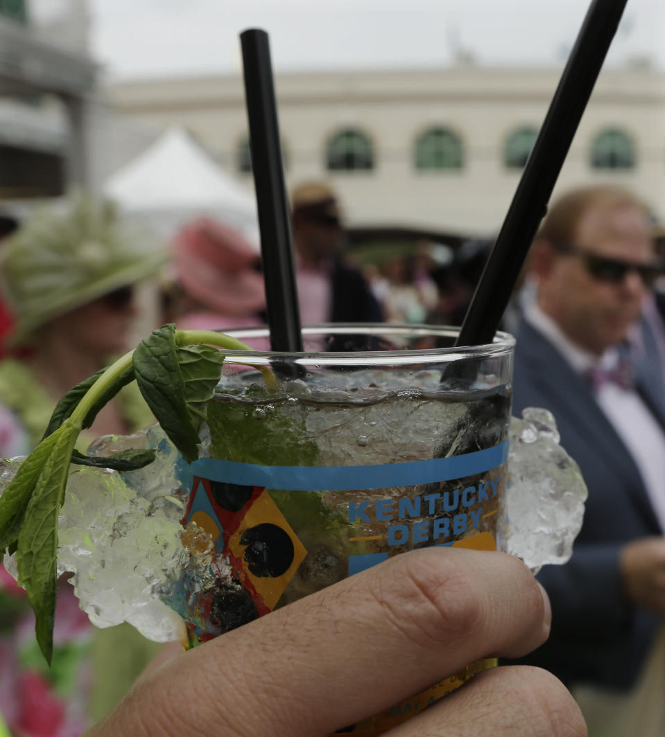 FILE - In this May 3, 2013, file photo, a spectator holds a mint julep before the running of the 139th Kentucky Oaks at Churchill Downs in Louisville, Ky. There will be no Run for the Roses on this first Saturday in May. The Kentucky Derby is one of the events that won't be held this week because of the coronavirus pandemic. (AP Photo/Charlie Riedel, File)