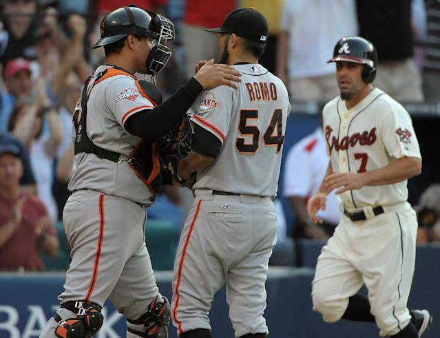 San Francisco Giants pitcher Sergio Romo (54) huddles with catcher Guillermo Quiroz after walking in Atlanta Braves' Reed Johnson for the tying run during the ninth inning of their baseball game at Turner Field, Saturday, June 15, 2013, in Atlanta. The Braves won 6-5. (AP Photo/David Tulis)