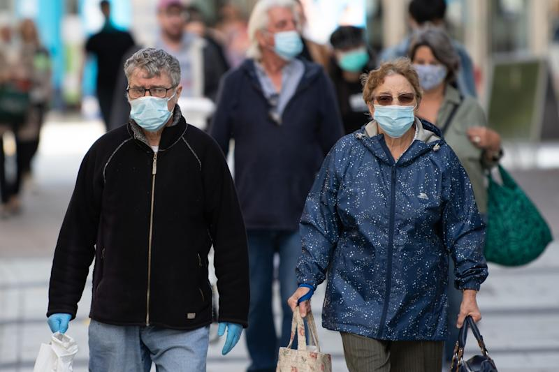CARDIFF, WALES - SEPTEMBER 23: A man and woman wear surgical face masks on Queen Street on September 23, 2020 in Cardiff, Wales. Four more counties in south Wales went into local lockdown this week, leaving more than a quarter of the Welsh population under tighter restrictions. Merthyr Tydfil, Bridgend, Blaenau Gwent and Newport now have the same restrictions as Rhondda Cynon Taf and Caerphilly where people cannot leave except for a limited number of exemptions. Additionally, pubs and bars will need to shut before 10pm. (Photo by Matthew Horwood/Getty Images)