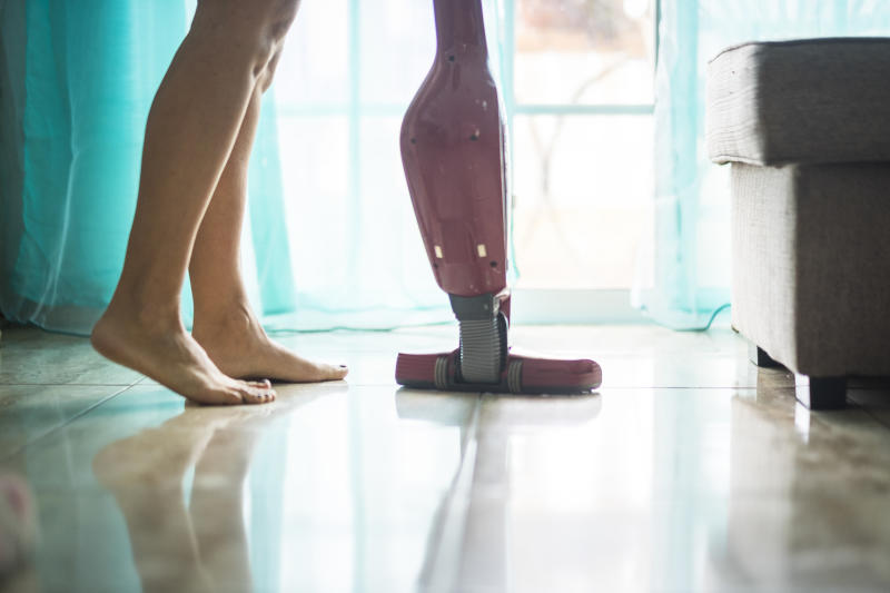 Nudism lifestyle concept for girl alone at home cleaning the floor with modern stuff - housewife lesire activity having care of the house walking barefoot - naked legs and mirror on the ground